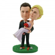 The smart groom holding up the comely bride custom bobblehead